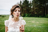 Bride blowing dandelion in nature. Young beautiful girl dispels dandelion on a green field outdoors. Happy wedding day of marriage.