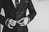 Man fastens the buttons. The groom in a suit, shirt, tie is standing on white background. Close up. Black and white photo.