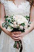 The bride in white dress are holding a beautiful wedding bouquet of pastel, pink, white peonies, roses flowers, greenery and decorated with ribbon on the background of greenery.