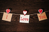 Text I love you. Craft paper, three blank, with red heart hanging on rope on brown wooden background with space. Place for text. concept of St. Valentine's Day. Women's Day, eighth of March.