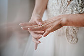The bride puts a wedding ring on finger. Close up of hands of woman showing elegant diamond ring on the finger, love and wedding concept. Engagement. Soft and selective focus.