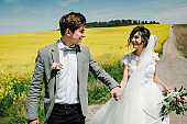 A newlywed wedding couple hold hands and walk on a  road, country for their honeymoon. Way on summer field of yellow rapes flowers, canola field.