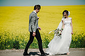 Bride and groom walk on the green and yellow field. wedding ceremony, country, outdoors. A newlywed wedding couple at wedding day.