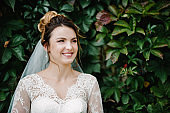 Portrait of beautiful bride near green wall with leaves on nature.