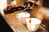 Espresso machine brewing a coffee. Coffee pouring into glasses in coffee shop, espresso pouring from coffee machine