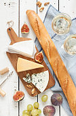 Different kinds of cheeses baguette and white wine