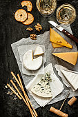 Different kinds of cheeses, white wine and snacks