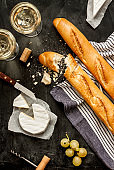 Camembert cheese, baguettes and wine on black