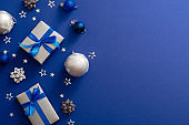 Christmas silver gift boxes or presents with bow ribbon, baubles, decorations, confetti on magic dark blue background with copy space. Vintage Xmas greeting card mockup, postcard template. Flat lay