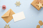 Empty blank card, kraft paper envelope on pastel blue background decorated with confetti star, gift box, wooden snowflakes, clew of rope. Christmas, New Year, winter holiday invitation mockup.