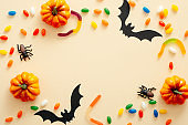 Halloween composition. Halloween decorations, pumpkins, candy, paper bats on pastel beige background. Halloween concept. Flat lay, top view, copy space