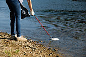 Volunteer woman picking up plastic garbage on coast of the river. Cleaning environment concept