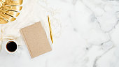 Beauty blogger workspace top view. Home office desk marble table with golden tropical monstera leaf, cup of coffee, gold paper notebook and pen. Flat lay, top view, copy space.