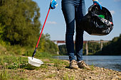 Volunteer woman picking up plastic litter on coast of the river. Cleaning environment concept