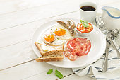 Full english breakfast on white plate and wooden table