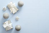 Silver Christmas festive decoration, baubles, gifts box with bow on pastel blue background. Merry Christmas and Happy Holidays greeting card, web banner mockup, postcard template.