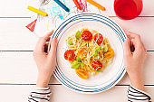 Meal (dinner) in child's hands - spaghetti with cherry tomatoes