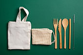 Zero waste, plastic free, eco friendly bamboo cutlery set and reusable canvas shopper bags. Sustainable lifestyle concept.