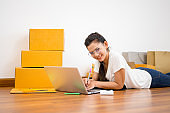 Beautiful teenager business owner work at home, alpha generation life style, prepare parcel box of product for deliver to customer