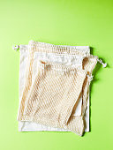 Empty cotton bags on green background