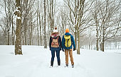 Smiling diverse couple exploring the nature on Canada while walking through a winter forest
