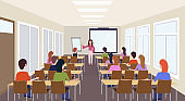 group of students listening female teacher training presentation modern meeting conference room interior lecture seminar hall education concept rear view horizontal