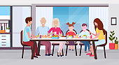 multi generation family sitting around table eating meal together happy grandparents parents and children modern kitchen interior flat horizontal