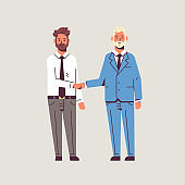 couple businessmen handshaking business partners hand shake during meeting agreement partnership concept male colleagues in formal wear standing together flat full length