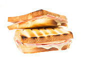 Two ham cheese toasts on each other on white background