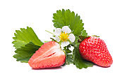 half and a whole strawberry with flower and leaves
