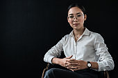 Portrait of an asian business woman sitting on chair isolated on black background