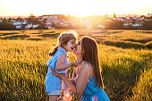 Young mother and daughter, hugging and playing in a golden field of sunshine.
