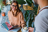 Waiter serving cup of coffee to smiling caucasian woman customer at coffee shop