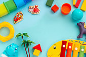 Top view of children educational games, frame kids toys blue paper background. Flat lay, copy space.