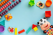 Сhildren's educational games, frame kids toys on blue paper background. Flat lay, copy space.