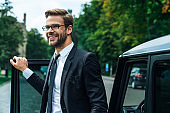 Handsome smiling young businessman coming out of his car while standing outdoors