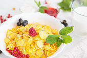 Fresh corn flakes with strawberries and milk close up Healthy tasty breakfast cornflakes with strawberries, raspberries, black currants and red currants.