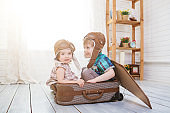 Little boy and girl in suitcase in the form of an aircraft pilot and traveler playing in room