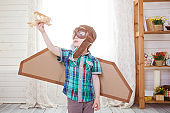 Little boy playing with wooden model airplane