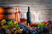 Red wine and white wine on wood table with grapes