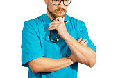 Mature doctor in glasses and blue medical clothes standing with crossed arms on isolation background. Medicine healthcare, decision making concept