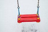Empty children's swing in the snow, swing on chains for the entertainment of children in winter