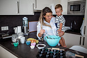 Young pretty mother bakes biscuits with her young son