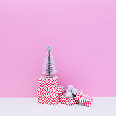 Winter holidays composition. Three sized gift boxes, decoration balls and fir tree on white and light pink background. Christmas and new year concept.
