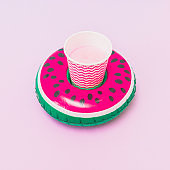 pool toy in shape of watermelon on pastel purple and blue background. Paper or plastic cup inside. Soft and bright colors