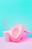 pool toy in shape of heart with wings on pastel pink and baby blue background. Paper or plastic cup and drinking straws near. Soft and bright colors
