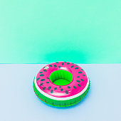 pool toy in shape of watermelon on pastel pink and turquoise background