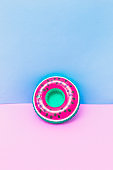 pool toy in shape of watermelon on pastel baby blue and flamingo pink background