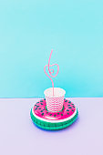 pool toy in shape of watermelon on pastel purple and blue background. Paper or plastic cup and drinking straw inside. Soft and bright colors