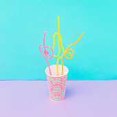 cup of tasty summer cold beverage with colorful drinking straws.